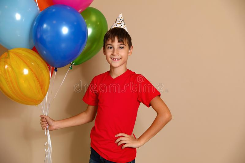 Happy boy with balloons on brown background stock image