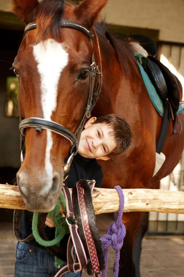 Happy boy with best friend. Happy little boy caressing horse, smiling, looking at camera stock photos