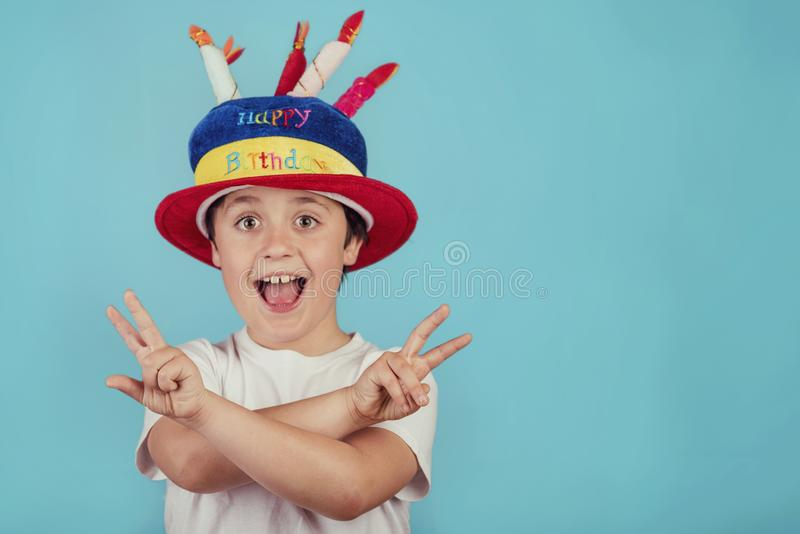 Happy boy with birthday hat. On blue background royalty free stock images
