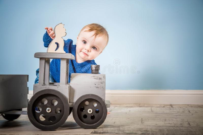 Happy boy blond in a blue sweater sits on a wooden floor. One year old baby playing with wooden toys. Cat and train made of wood stock images