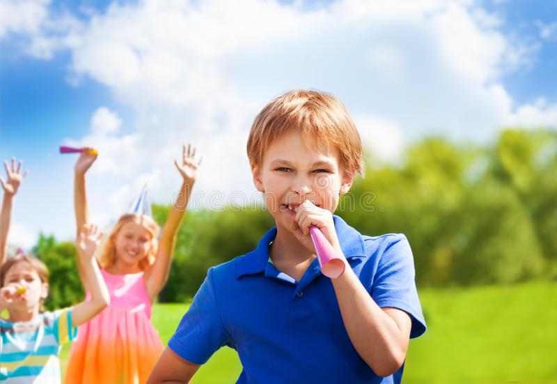 Happy boy blows horn on birthday party. One happy boy blows noisemaker horn on a birthday party wearing cap with friends standing on background royalty free stock images