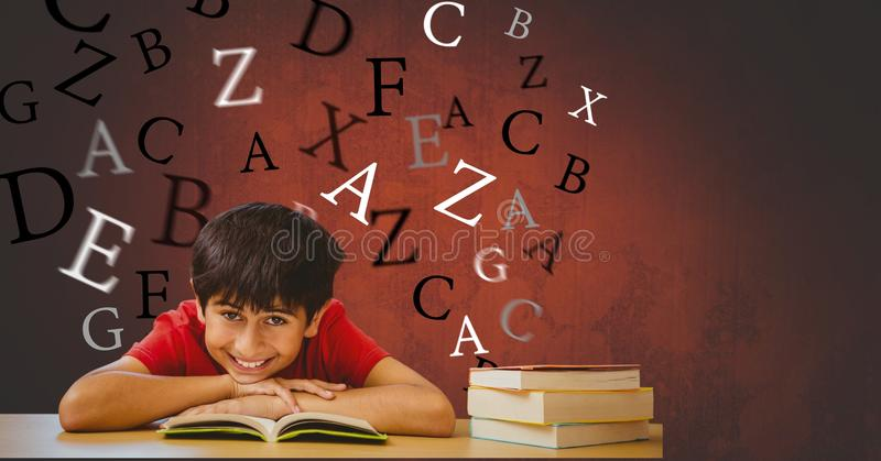 Happy boy with book leaning on table against flying letters. Digital composite of Happy boy with book leaning on table against flying letters royalty free stock image