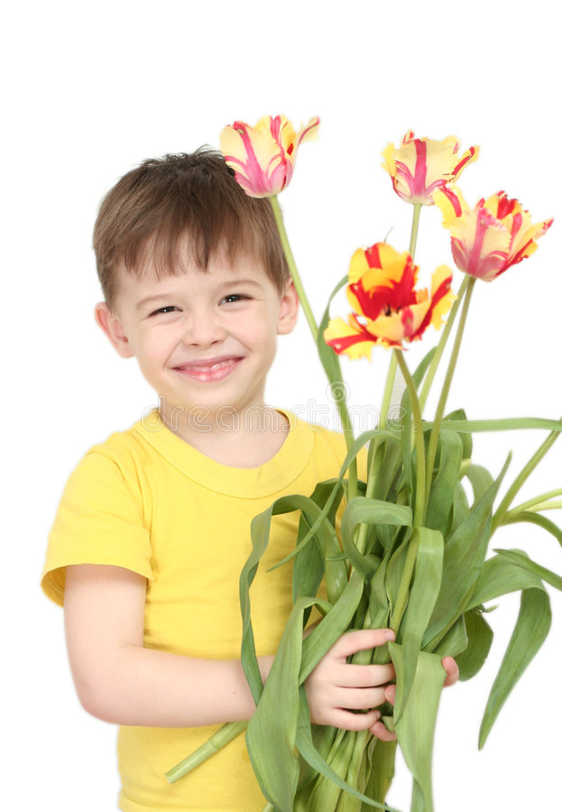 The happy boy with a bouquet of tulips royalty free stock image