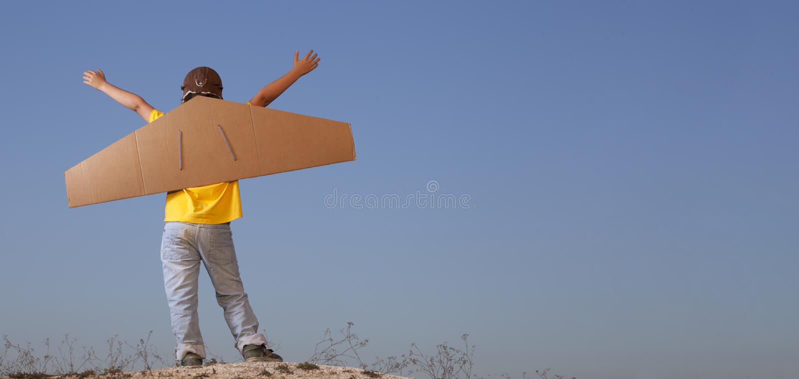 Happy boy with cardboard boxes of wings against sky dream of fly royalty free stock photos