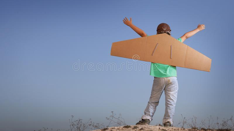 Happy boy with cardboard boxes of wings against sky dream of flying stock photography