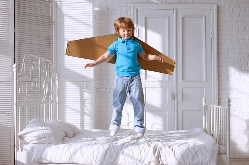 Happy boy with cardboard boxes of wings in home dream of flying.  royalty free stock images