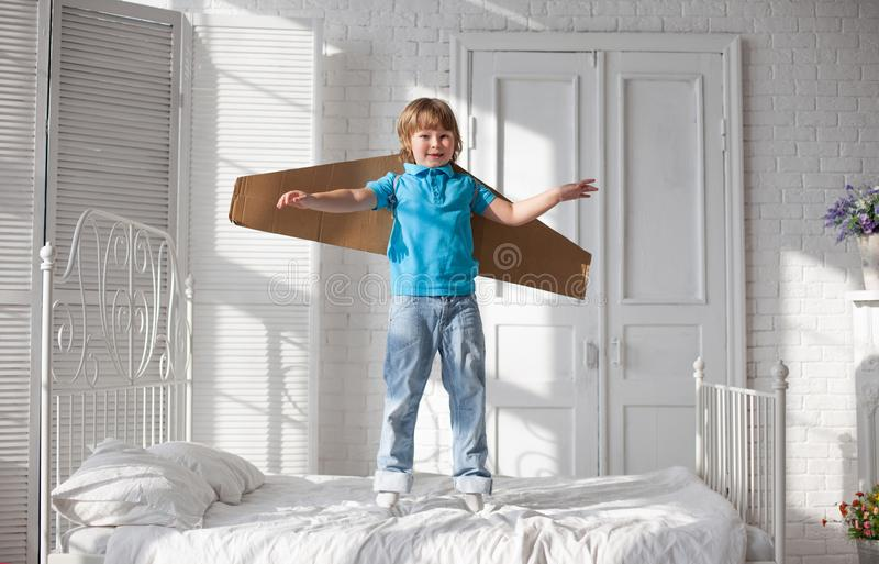 Happy boy with cardboard boxes of wings in home dream of flying.  royalty free stock photography