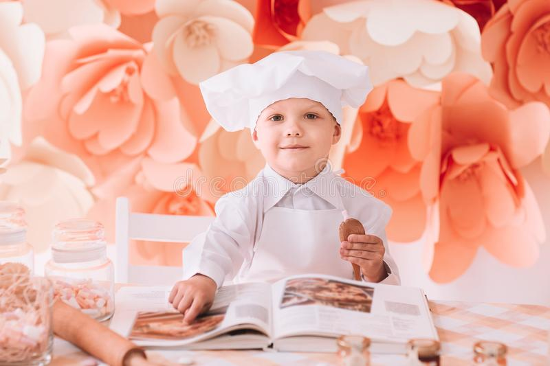 Happy boy chef chooses a cooking recipe. The concept of a hobby royalty free stock photos