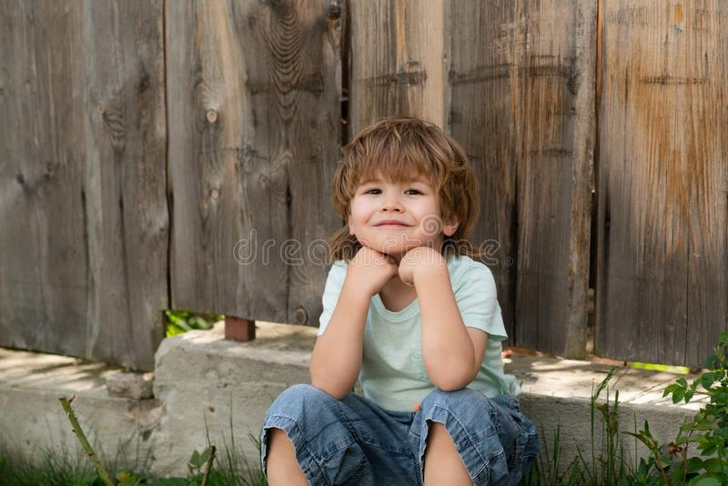 Happy boy. A child with a smile. Kid sits near a wooden fence. Happy summer. August or September. stock images