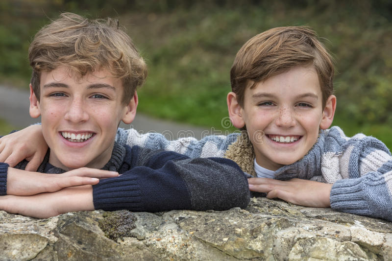 Happy Boy Children Brothers Smiling Together. Outside leaning on a wall royalty free stock image