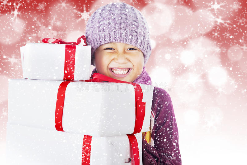 Happy boy with christmas boxes on defocused light. Boy with beany holding white christmas boxes on red defocused lights royalty free stock photography