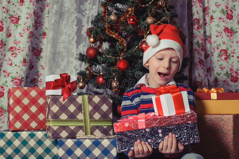 Happy boy with christmas present boxes royalty free stock image