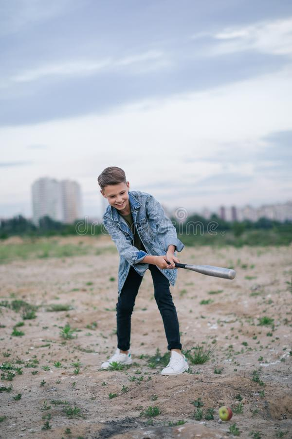 Happy boy in denim jacket playing with baseball bat. At cloudy day stock photos