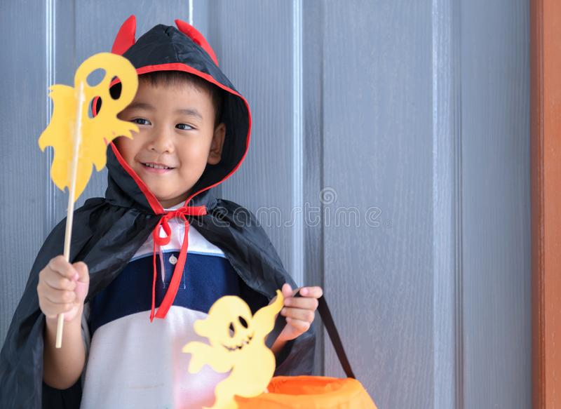 Boy devil smile and playing paper ghost stock images