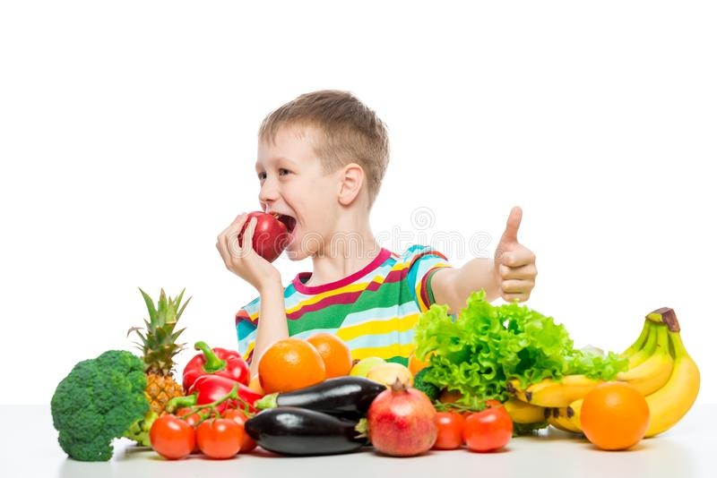 Happy boy on a diet with food, eating a red apple sitting stock image