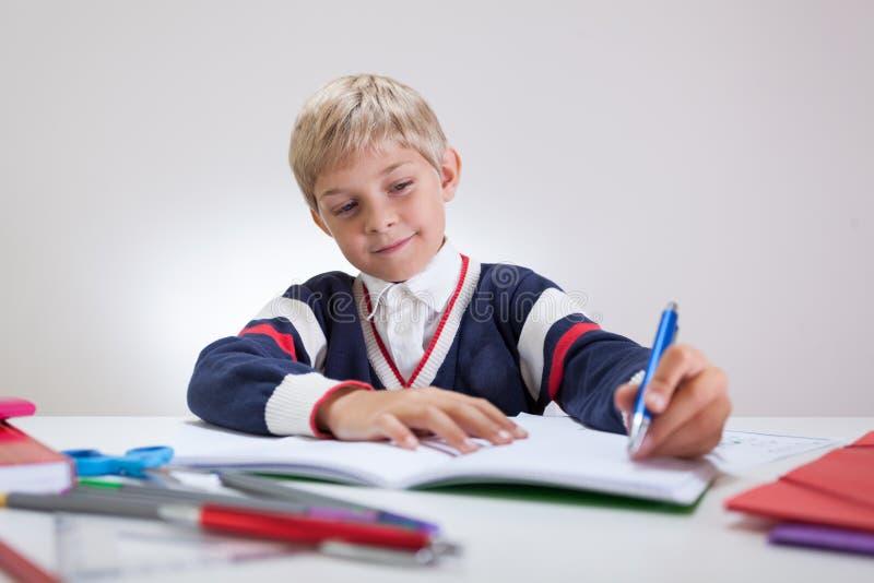 Happy boy doing homework. Horizontal view of happy boy doing homework royalty free stock images