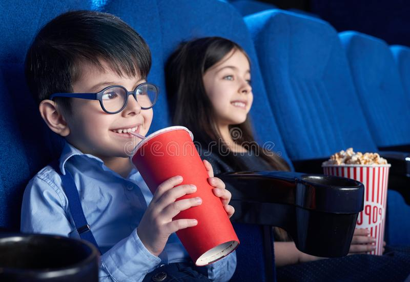 Happy boy drinking aerated sweet water and watching movie. View from side of happy boy wearing glasses drinking aerated sweet water and watching interesting stock photos