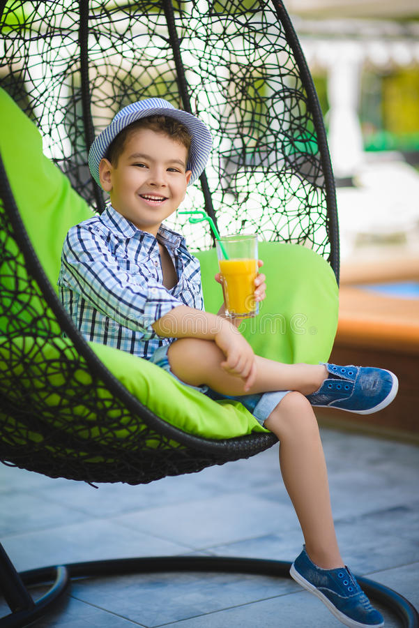 Happy boy drinking juice in resort restaurant outdoor royalty free stock images
