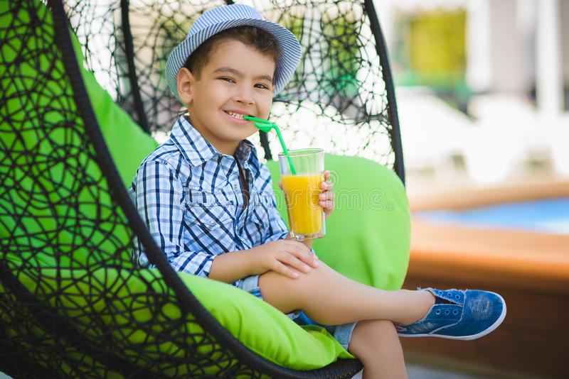 Happy boy drinking juice in resort restaurant outdoor royalty free stock photography