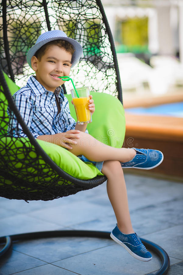 Happy boy drinking juice in resort restaurant outdoor royalty free stock photo