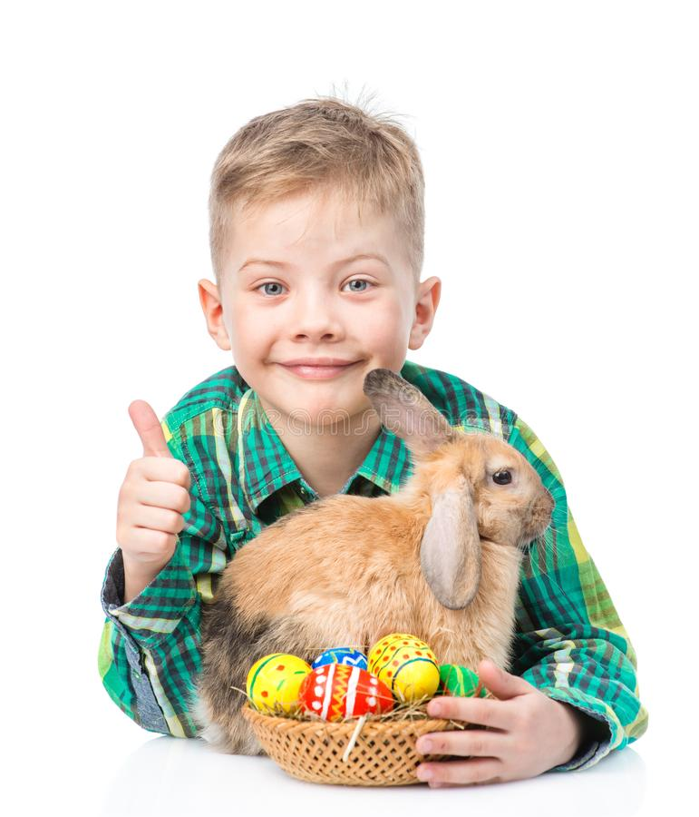 Happy boy with easter eggs embracing rabbit and showing thumbs up. Isolated on white background stock photo