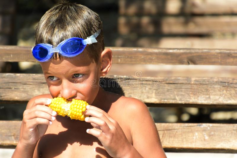 Happy boy wearing swimming goggles eating corn on the cob. Summer weekend stock photo