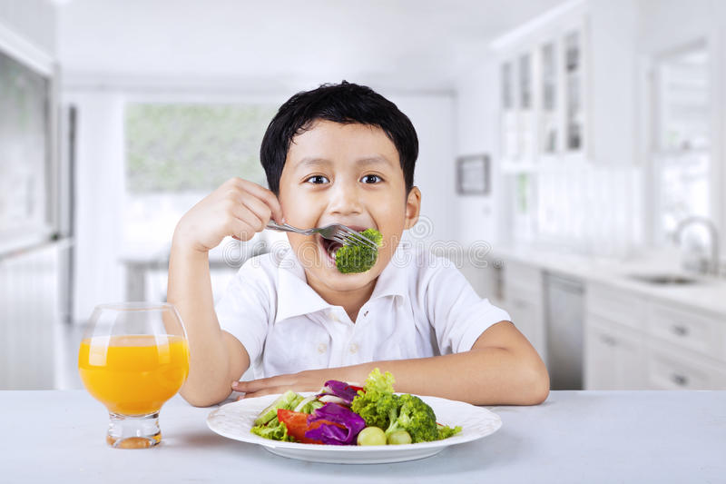 Boy eating broccoli at home stock photo