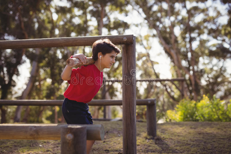 Happy boy exercising with log while listening music during obstacle course stock images
