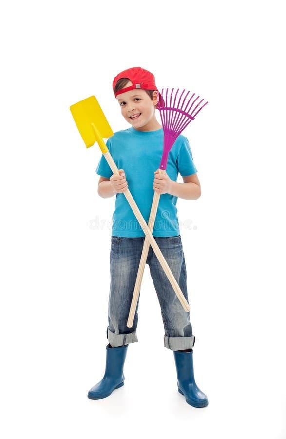 Happy boy with gardening tools stock photo