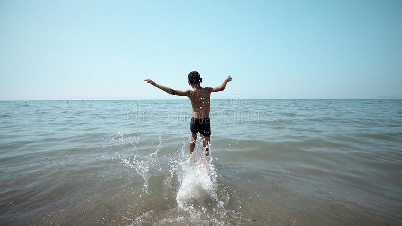 Happy boy getting int the sea water. Front cinematic steadicam view royalty free stock images