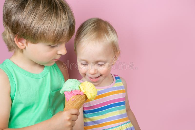Happy boy and girl eating ice cream in front of pink bakground stock photography