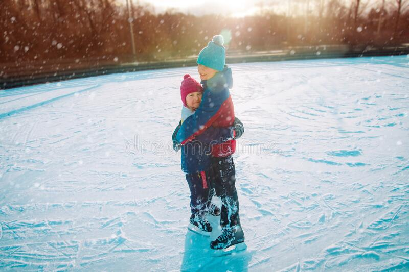 Happy boy and girl hug while skating together, kids winter sport. Happy boy and girl hug while skating together, kids enjoy winter sport stock image