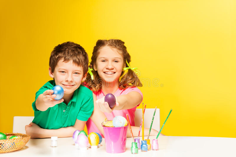 Happy boy and girl show Easter eggs on the table. On the yellow background royalty free stock photography