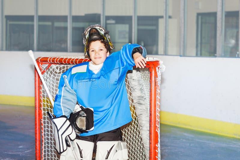 Happy boy goaltender posing after hockey match. Portrait of teenage boy goaltender, standing next to the net after hockey match smiling stock image