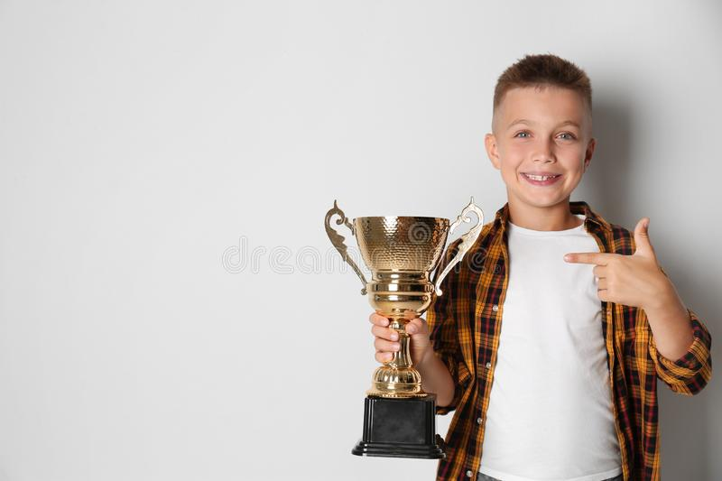 Happy boy with golden  cup on light background. Space for text stock photo