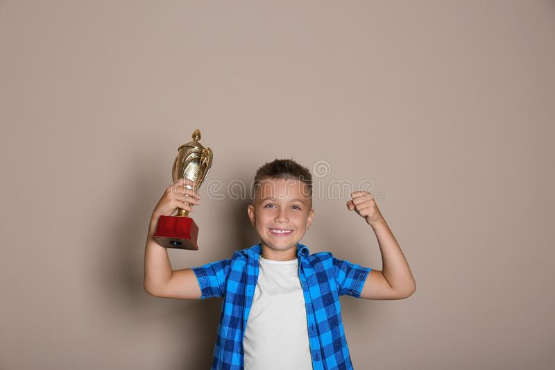 Happy boy with golden winning cup on background. Happy boy with golden winning cup on beige background stock photos