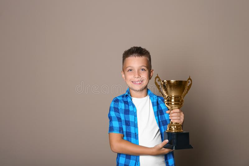 Happy boy with golden winning cup on beige background. Space for text stock photos