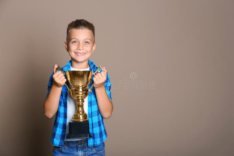 Happy boy with golden winning cup on background. Space for text. Happy boy with golden winning cup on beige background. Space for text stock image