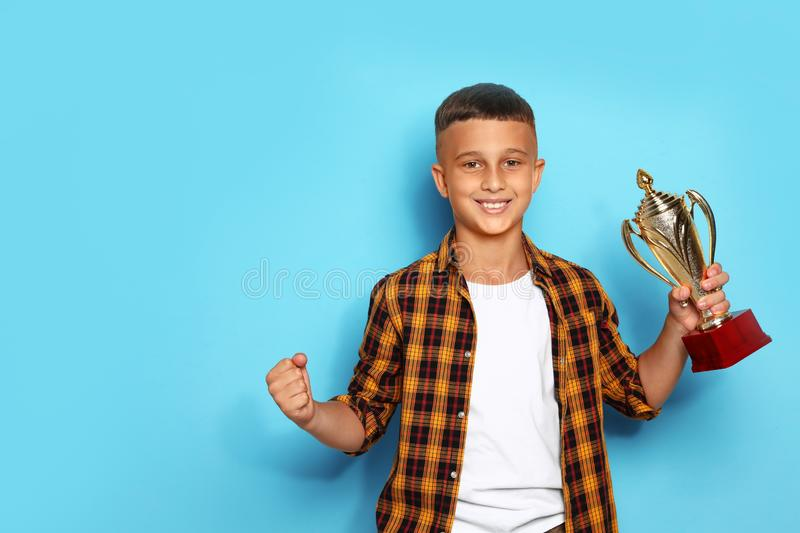 Happy boy with  winning cup on blue background. Happy boy with golden winning cup on blue background royalty free stock image