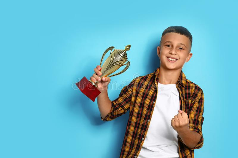 Happy boy with golden winning cup on background. Happy boy with golden winning cup on blue background stock image