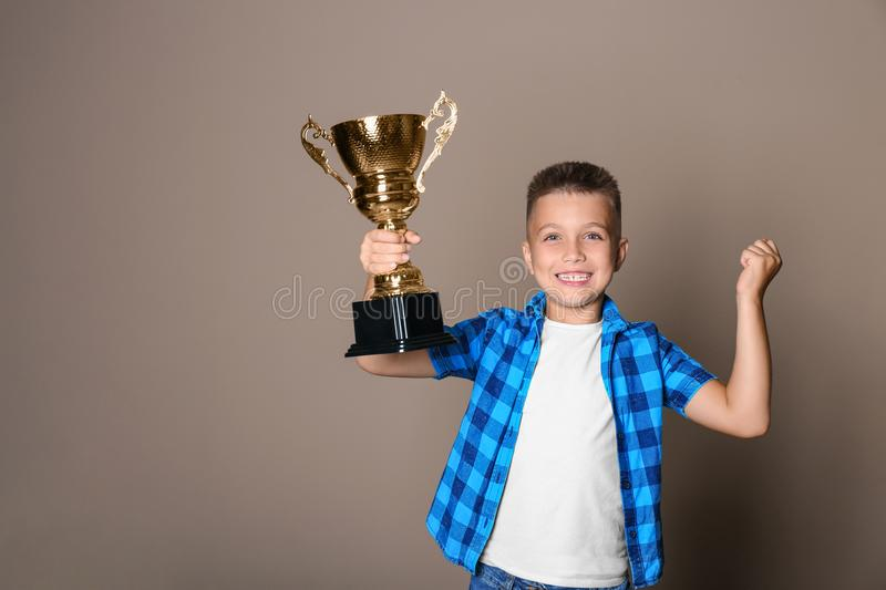 Happy boy with golden winning cup. On beige background royalty free stock photo