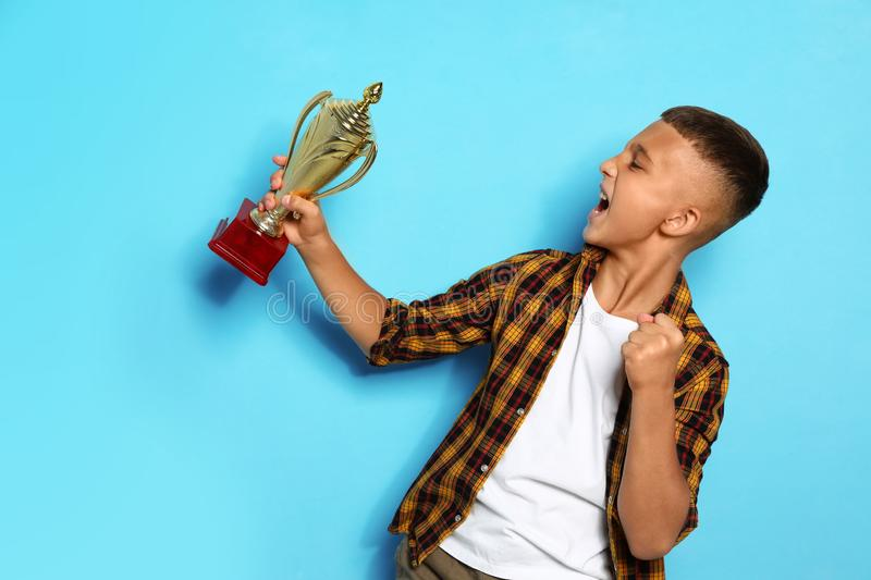 Happy boy with golden winning cup. On blue background royalty free stock images