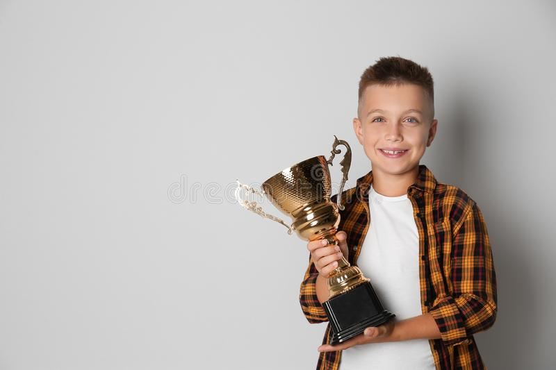 Happy boy with golden winning cup on light background royalty free stock image