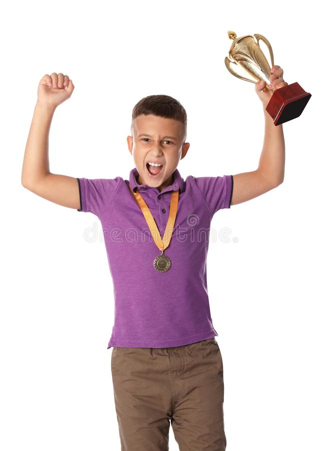 Happy boy with golden winning cup and medal on background. Happy boy with golden winning cup and medal on white background royalty free stock images