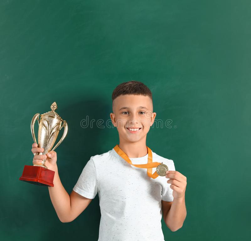 Happy boy with golden winning cup and medal. Near chalkboard royalty free stock photos