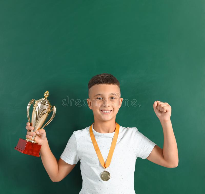 Happy boy with golden winning cup and medal. Near chalkboard stock photography