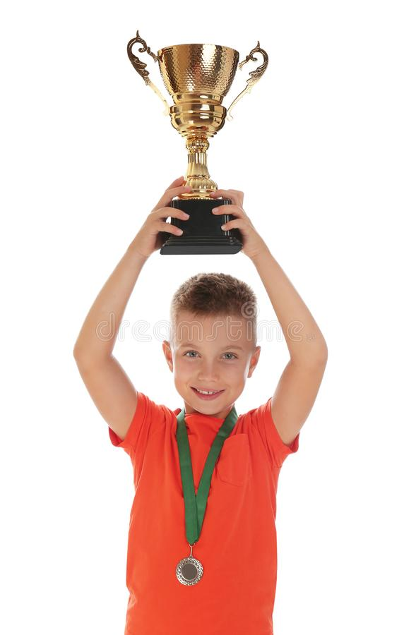 Happy boy with golden winning cup and medal on white. Happy boy with golden winning cup and medal isolated on white stock images