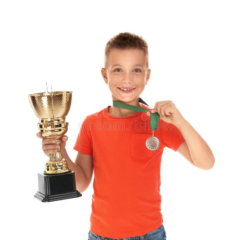 Happy boy with golden winning cup and medal on white. Happy boy with golden winning cup and medal isolated on white royalty free stock photography