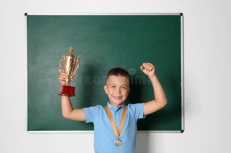 Happy boy with golden winning cup and medal near chalkboard. In classroom stock image