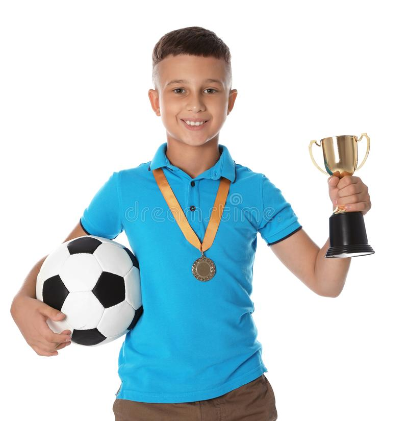 Happy boy with golden winning cup, medal and soccer ball. On white background stock photo